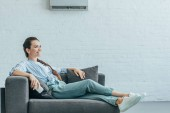 Fotografie happy woman relaxing on sofa with air conditioner on white wall, summer heat concept