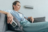 Fotografie woman resting on sofa with air conditioner remote control, summer heat