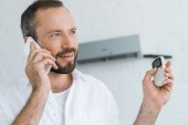 Fotografie bearded man talking on smartphone while turning on air conditioner with remote control