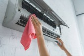 Fotografie cropped view of female worker cleaning air conditioner with rag