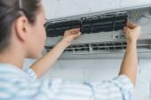 Fotografie selective focus of female worker repairing air conditioner
