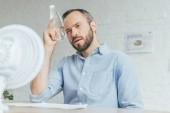 Fotografie podnikatel sám s lahví vody chlazení a klimatizace vzduchu s elektrickým ventilátorem v úřadu