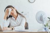 Fotografie zpocený podnikatelka pracující v kanceláři s elektrickým ventilátorem