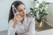Fotografia upset businesswoman cooling herself with cold bottle of water in hot office