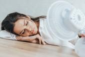 Fotografie vyčerpání podnikatelka se zavřenýma očima, foukání na sebe s elektrickým ventilátorem v úřadu