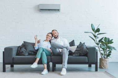 couple turning on air conditioner during the summer heat at home