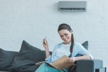 woman turning on air conditioner with remote control while reading book on sofa