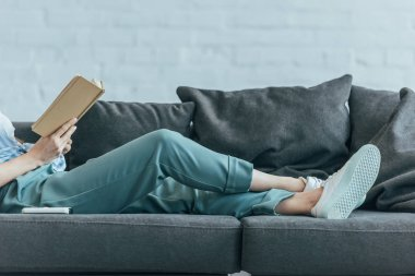 cropped view of woman relaxing on sofa and reading book