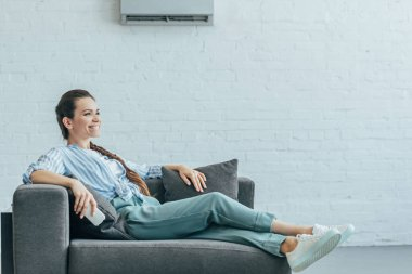 happy woman relaxing on sofa with air conditioner on white wall, summer heat concept