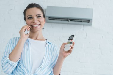 smiling woman talking on smartphone while turning on air conditioner with remote control