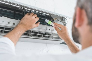 selective focus of repairman cleaning air conditioner with brush