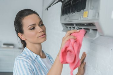 woman cleaning air conditioner with rag