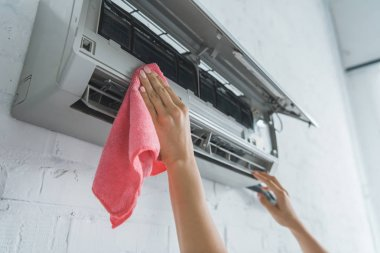 cropped view of female worker cleaning air conditioner with rag