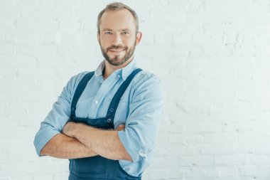 smiling bearded worker in overalls posing with crossed arms