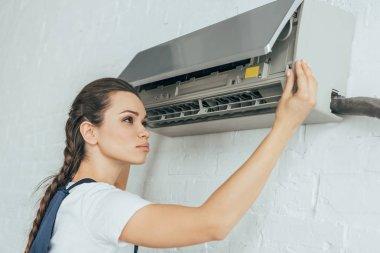 Beautiful female worker repairing air conditioner stock vector