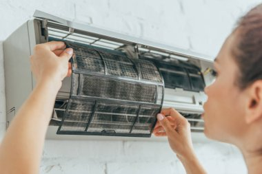 selective focus of female worker repairing air conditioner