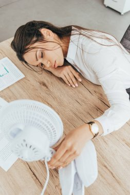 exhausted businesswoman blowing at herself with electric fan in office