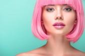 Fotografie Detailní portrét mladé ženy s růžové bob střih, při pohledu na fotoaparát izolované na tyrkysové