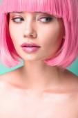 Fotografie Detailní portrét mladé ženy s růžové bob střih, při pohledu na straně izolované na tyrkysové