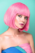 seductive young woman with pink bob cut looking at camera isolated on turquoise