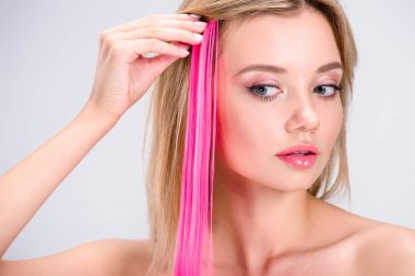 attractive young woman applying pink clip-on hair strand isolated on grey