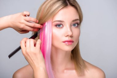 cropped shot of hair stylist working with attractive young woman isolated on grey