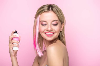 happy young woman with colorful strands of hair and spray paint isolated on pink