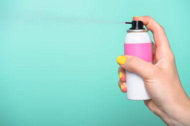 cropped shot of woman holding spray paint for hair isolated on turquoise