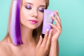Fotografie sensual young woman with colorful hair holding hair tonic tube isolated on blue