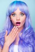 šokovaná mladá žena pokrývající ústa rukou a při pohledu na fotoaparát izolované na modré