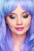 close-up portrait of sensual young woman with blue hair looking down isolated on blue