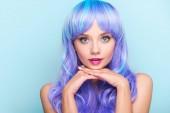 elegantní mladá žena s modrými vlasy při pohledu kamery na modré, samostatný