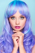 krásná mladá žena s modrými vlasy při pohledu kamery na modré, samostatný