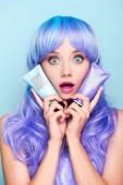 döbbenve, fiatal nő, a színező a haj tonik elszigetelt kék csövek