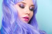 Detailní portrét atraktivní mladá žena s kudrnatými vlasy modré izolované na modré