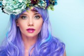 Fotografie close-up portrait of beautiful young woman with curly blue hair and floral wreath isolated on blue