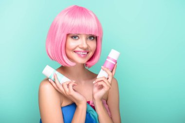 beautiful young woman with pink bob cut holding cans of coloring hair sprays isolated on turquoise