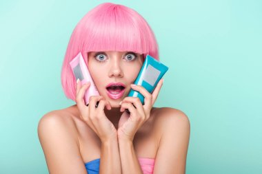 shocked young woman with tubes of coloring hair tonics looking at camera isolated on turquoise