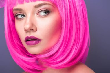 beautiful young woman with pink bob cut isolated on violet