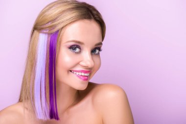 close-up portrait of happy young woman with stylish makeup and purple hair strands isolated on purple