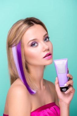 attractive young woman with bobbed hair with purple strands and coloring hair tonic looking at camera isolated on blue