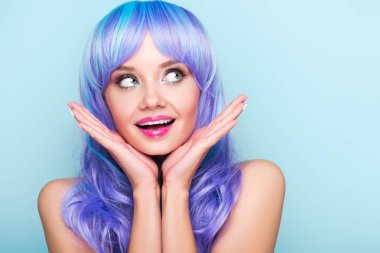 excited young woman with blue hair looking looking away isolated on blue