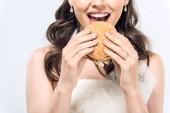 oříznutý snímek hlad mladá nevěsta ve svatebních šatech jíst hamburger izolované na bílém