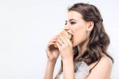Nahaufnahme Porträt einer hungrigen jungen Braut im Hochzeitskleid, die isoliert auf Weiß Hamburger isst