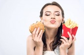 young bride in wedding dress with burger and french fries sending kiss at camera isolated on white