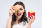 šťastná mladá nevěsta ve svatebních šatech s burger a hranolky, izolované na bílém