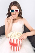 Fotografie angry young bride in wedding dress and 3d goggles eating popcorn on couch isolated on white