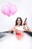 Fotografie happy young bride in wedding dress with beer and bucket of popcorn watching movie isolated on white