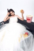 depressed young bride in wedding dress sitting on couch with beer and junk food on white