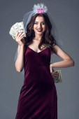 Fotografie beautiful future bride in veil for bachelorette party holding cash and looking at camera isolated on grey